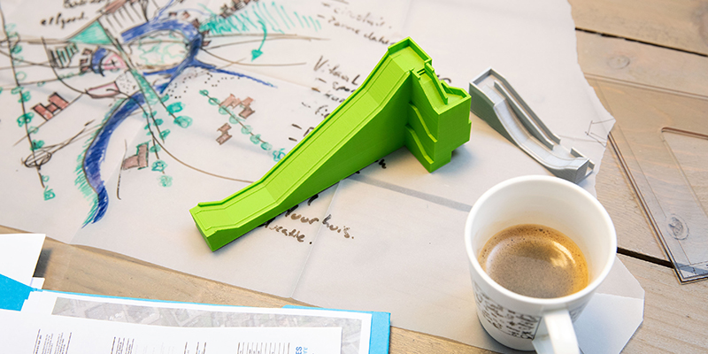 Table with a concept drawing, a ramp model and a cup of coffee